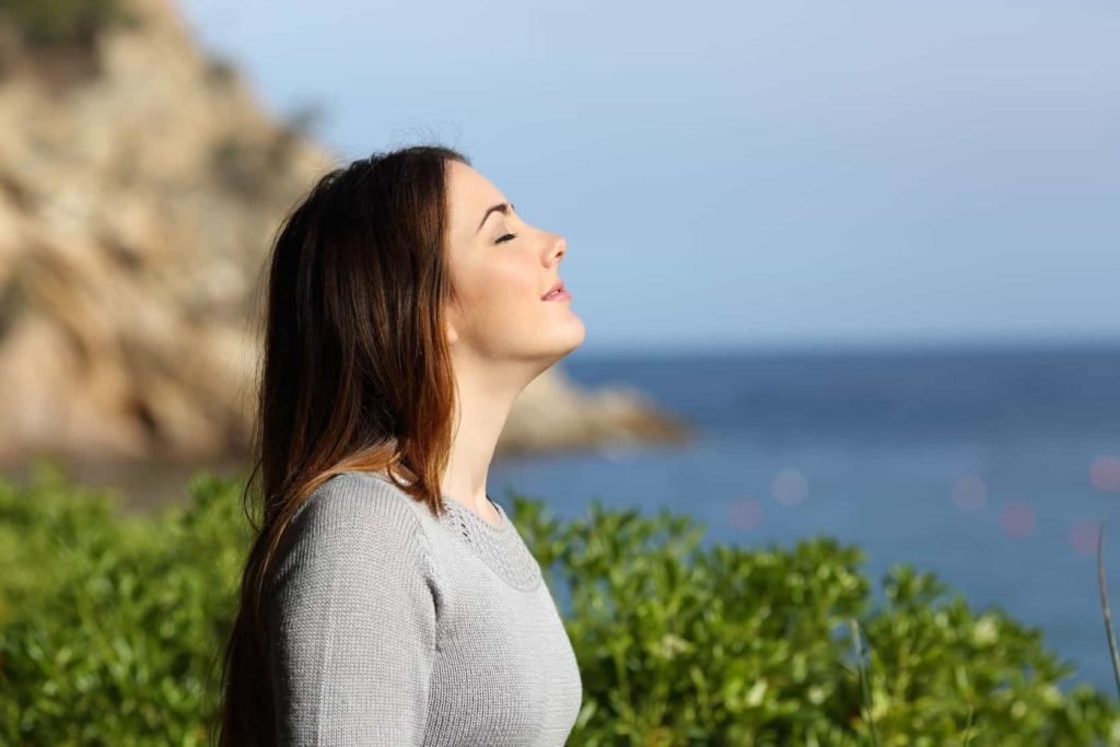 Photo for Anxiety - Practical Intervention Strategies. Woman on coast breathing deeply
