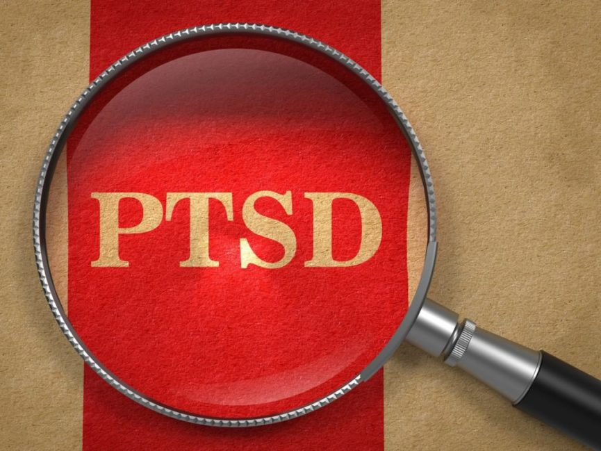 PTSD written beneath magnifying glass