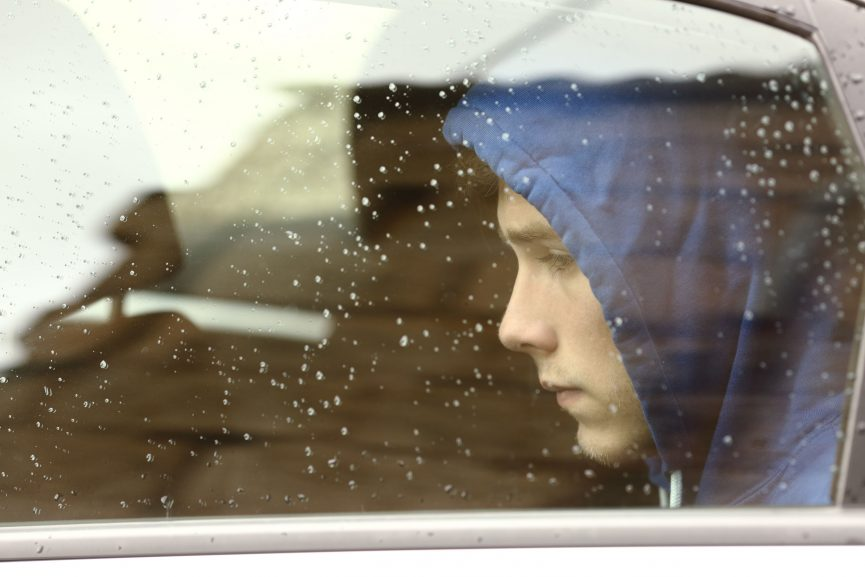 sad teenager looking through car window