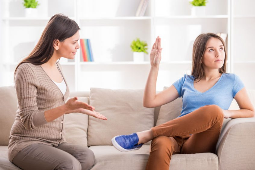 teen girl is showing stop gesture to angry mother while sitting on sofa at home.
