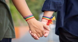 Image of two people holding hands with rainbow bracelets on Gender and Sexual Diverse Youth – Embracing and Supporting